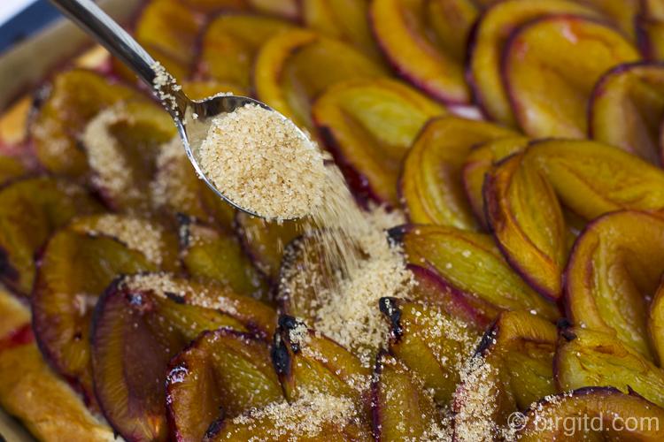 Pflaumenkuchen nach dem Backen mit Zucker bestreuen