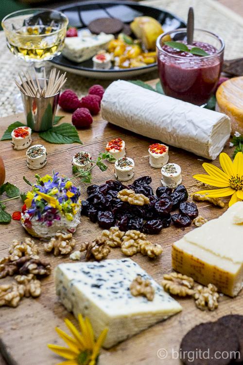 Käseplatte mit Ziegenkäserolle, Walnüssen und getrockneten Früchten