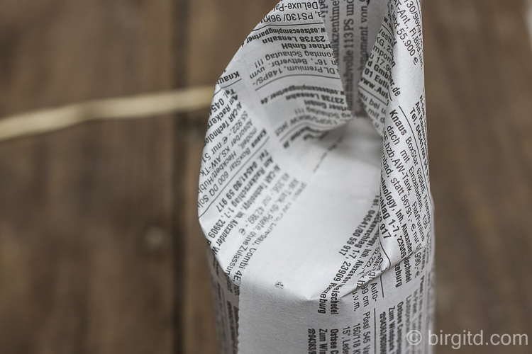 Das überstehende Papier rundherum, wie beim Einpacken von Geschenken, zur Mitte hin falten - dabei mit der offenen, losen Seite beginnen