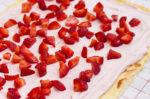 Joghurt-Sahnemischung und kleingeschnittene Erdbeeren auf dem Teig verteilt