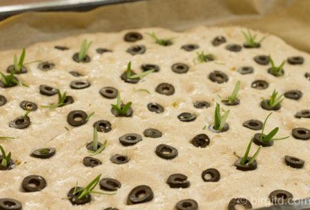 Focacciazteig mit Belag aus Oliven, Rosmarin und Meersalz